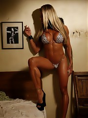 Blonde bodybuilder Larissa Reis has some flowery tattoos twining around her pecs, arms and legs as she poses in the bedroom, giving you a look at her sexy, muscular glutes, calves and biceps and her ripped, vascular abs. But don't let that fool you. She's tough as can be, and those bulging blossoms prove it.